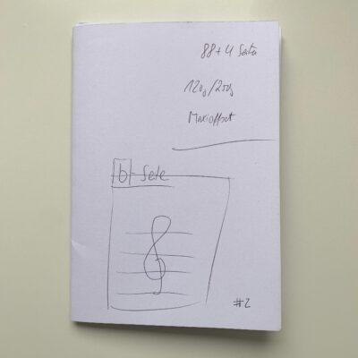 """Das ist ein Foto eines b-seite-Probeexemplars, ein weißes Heft auf das mit der Hand """"b-seite 2"""" geschrieben wurde"""