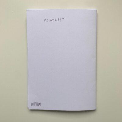 """Hier ist die Rückseite des leeren Heftes. Darauf steht """"Playlist"""" geschrieben."""